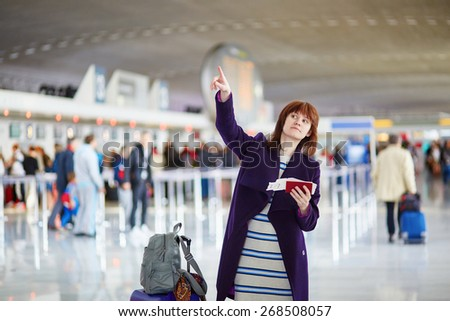 Beautiful young female passenger at the airport, looking for something - stock photo