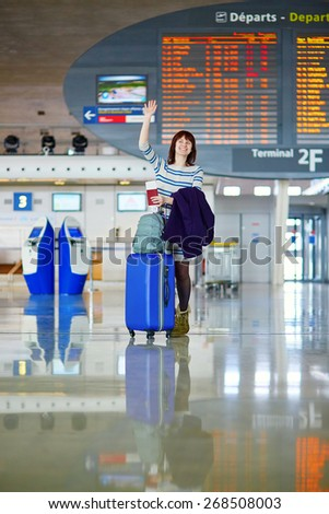 Beautiful young female passenger at the airport, waving to someone - stock photo