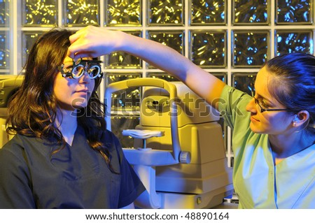 Beautiful young female patient having a medical examination at optician - a series of dramatically lightened eye exam related pictures. - stock photo