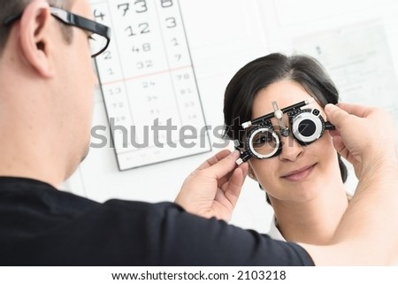 Beautiful young female patient is having a medical attendance at the optometrist. - stock photo