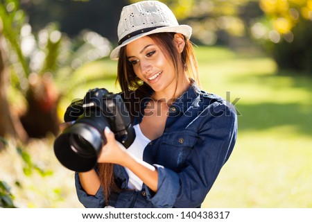 beautiful young female photographer checking pictures on her camera - stock photo