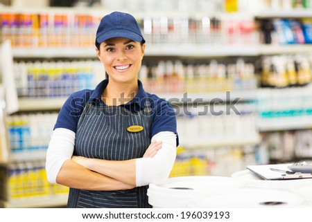 beautiful young female supermarket worker with arms crossed - stock photo