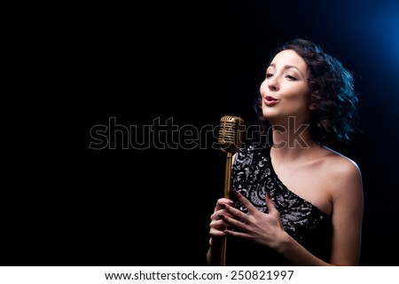 Beautiful young female vocalist in shiny black evening dress singing with emotions behind golden retro microphone, during live musical show, copy space - stock photo