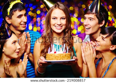Beautiful young female with birthday cake looking at camera, her friends applauding - stock photo