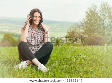 Beautiful young female with earphones outdoors enjoying music and smiling while sitting down on grass with copyspace - stock photo