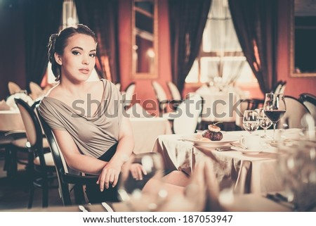 Beautiful young girl alone in a restaurant - stock photo