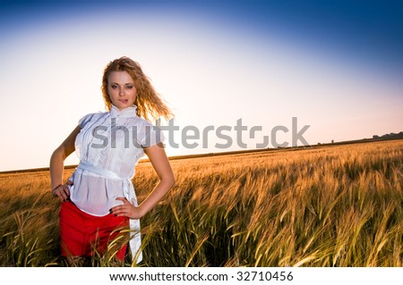 Beautiful young girl at golden field - stock photo