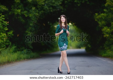 beautiful young girl, brunette with long straight Voros with beautiful breasts and long legs standing on the road against the background of green trees - stock photo