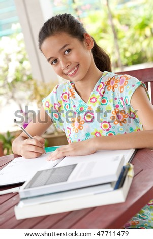 Beautiful young girl doing her homework in a home environment - stock photo