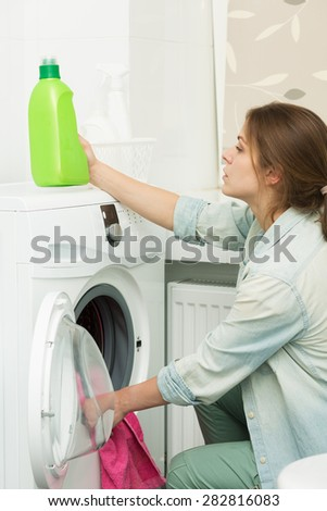 Beautiful young girl doing laundry at home - stock photo