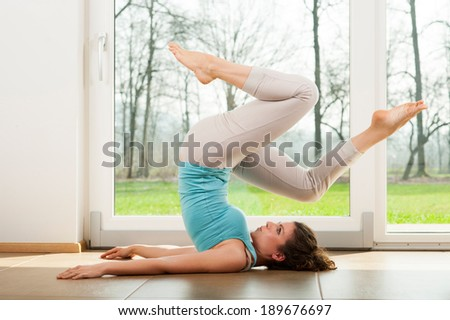 Beautiful young girl doing yoga exercise in front of the window. Human wheel. Indoor. - stock photo