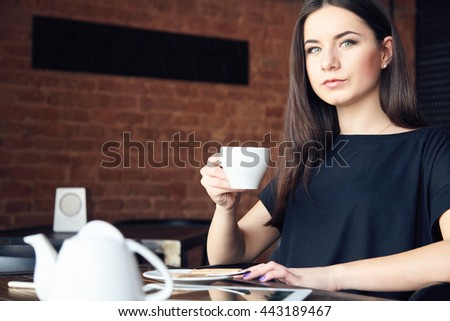 Beautiful young girl drinking tea in cafe and holding cup in hand. Portrait of gorgeous woman thoughtfully looking at camera in coffee shop while enjoying her leisure time alone. - stock photo