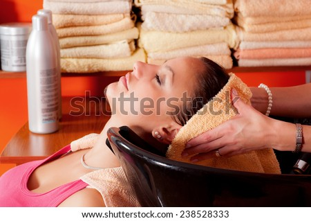 Beautiful young girl enjoying hair washing in hairdressing salon. - stock photo