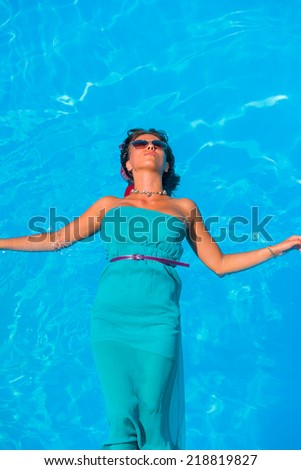 Beautiful young girl floating in pool on her back on a hot summer day - stock photo