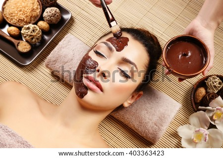 Beautiful young girl getting chocolate mask in spa salon - stock photo