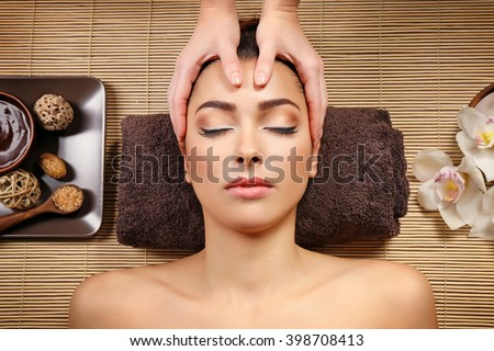 Beautiful young girl having face massage in spa salon - stock photo