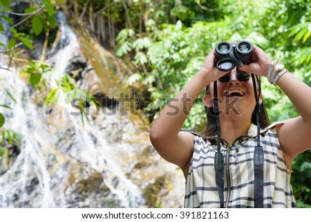 Beautiful young girl hiking is using binoculars look for birds in tropical forest near the waterfalls in Thailand - stock photo
