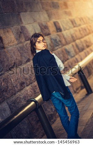 beautiful young girl hipster goes along a brick wall - stock photo