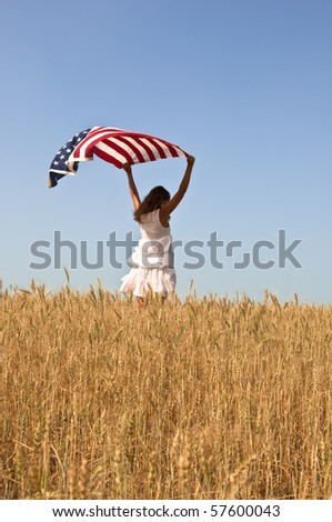 Beautiful young girl holding an American flag in the wind in a field of rye. Summer landscape against the blue sky. Vertical orientation. - stock photo