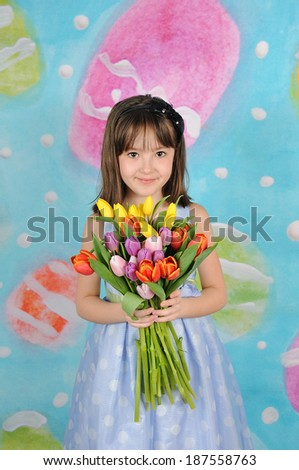 beautiful young girl holding bouquet of tulips at easter - stock photo