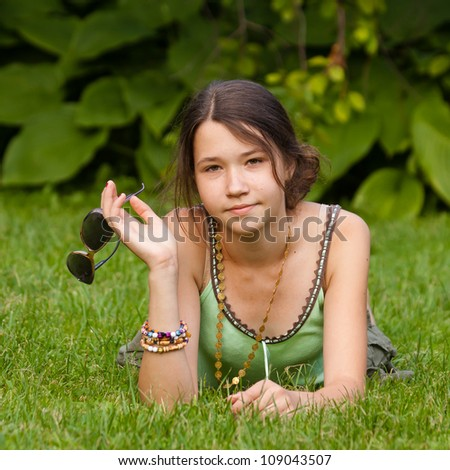 Beautiful young girl holding sunglasses in the park - stock photo