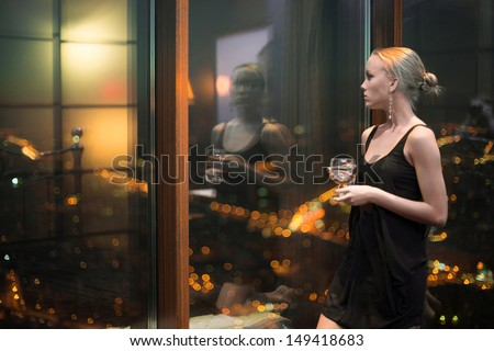 Beautiful young girl in a black dress with glass in the bedroom near the window - stock photo