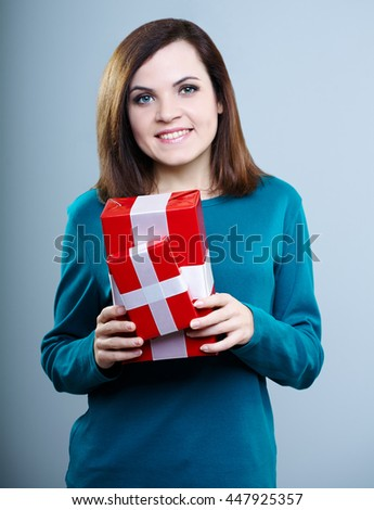beautiful young girl in a blue t-shirt holding gift boxes on gray background - stock photo