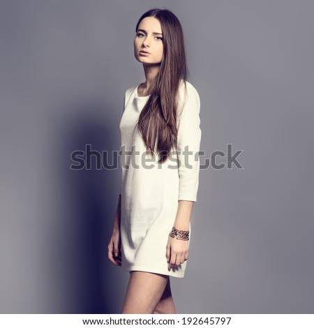 Beautiful young girl in a dress in the studio - stock photo