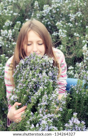 beautiful young girl in a grass field of rosemary - stock photo