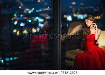 Beautiful young girl in a red dress in the apartment - stock photo
