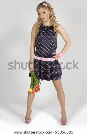 Beautiful young girl in a shot dress with tulip - stock photo