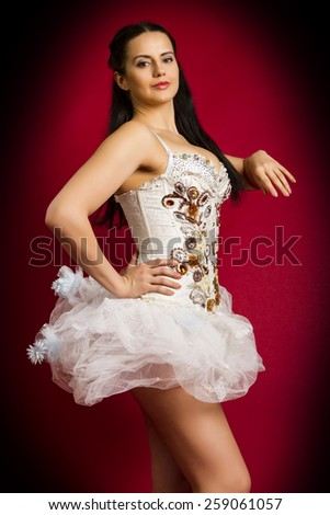 beautiful young girl in a white sexy dress on a red background - stock photo