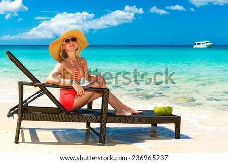Beautiful young girl in bikini is sitting on a sun lounger coast of tropical sea. Summer vacation concept. - stock photo
