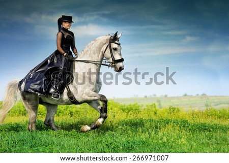 Beautiful young girl in black dress riding a gray horse - stock photo