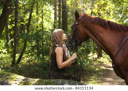 Beautiful young girl in brown dress and chestnut horse at the forest - stock photo