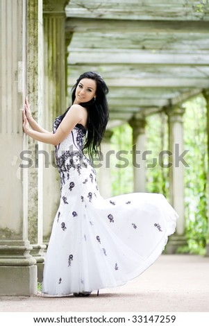 Beautiful young girl in elegant dress in ancient summerhouse - stock photo