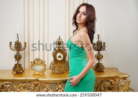 Beautiful young girl in green dress with big breasts, full lips, slim, athletic build,� , brunette, in the interior of the Renaissance in beige and golden tones - stock photo