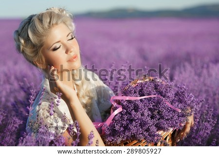 Beautiful young girl in lavender field, happy woman enjoying lavender flowers in summer sunset, pretty female girl relaxing outdoor having fun, aromatherapy and spa concept, series - stock photo