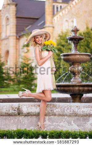 Beautiful young girl in light dress in the fabulous garden, holding bouquet of sunflowers  - stock photo
