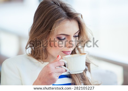 beautiful young girl in outdoor cafe reading a book and drinking coffee. phone. student. business woman - stock photo