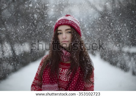 Beautiful young girl in red Christmas clothes on the street in the snow. Fashion photo. - stock photo