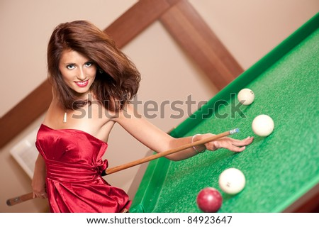 Beautiful young girl in red dress playing a billiards. - stock photo