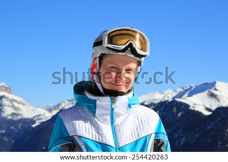 Beautiful young girl in sports ski clothes, helmet on his head and a mask on a background of mountains - stock photo
