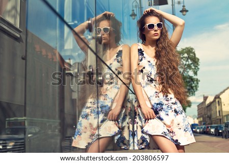 beautiful young girl in summer time wearing dress and sunglasses posing on the street - stock photo