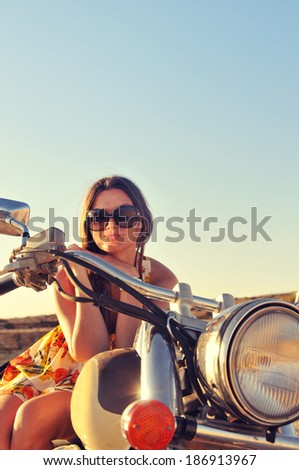 Beautiful young girl in sunglasses sitting on a motorcycle near a rocky seashore - stock photo