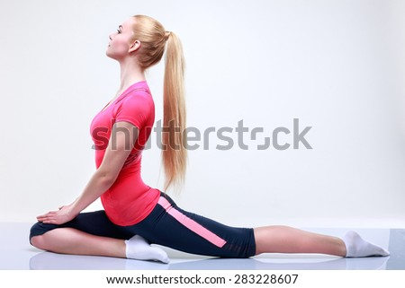 Beautiful  young girl is engaged in a fitness, on a light-grey background - stock photo