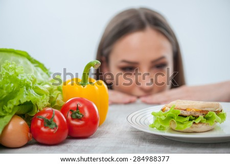 Beautiful young girl is looking at the hamburger with appetite. She makes her decision to eat it and does not look at vegetables. Focus on hamburger and vegetables. Isolated on a white background - stock photo