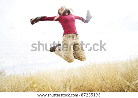 Beautiful young girl jumping with joy in a long grass field - stock photo