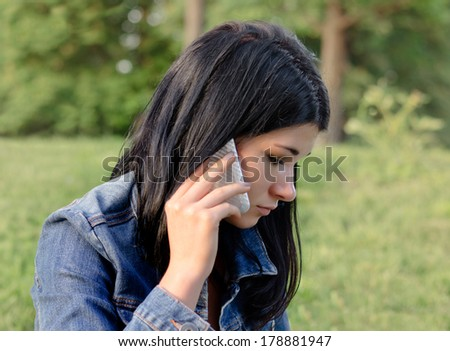 Beautiful young girl listening to a call on her mobile with a serious concerned expression as she stands outdoors in a denim jacket in a park - stock photo