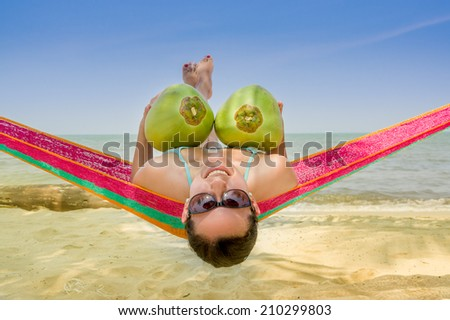 Beautiful young girl lying in a hammock holding two coconuts - stock photo
